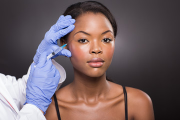 cosmetic surgeon injecting african american girl face