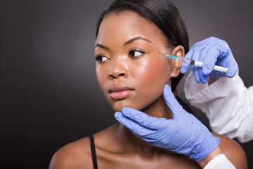 afro american woman receiving plastic surgery injection on her f