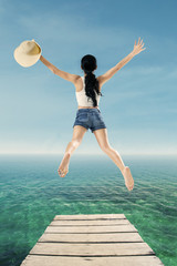 Woman enjoy freedom by jump at pier