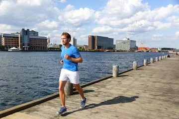 Running man jogging in modern city