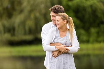 young man hugging girlfriend outdoors
