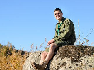 Smiling Handsome Boy Scout Sitting on the Rock
