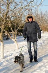 Man walking his dog in winter snow