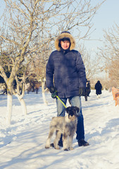Adult Man with his Dog Standing at the Snow