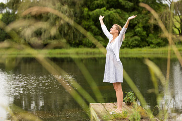 young woman with arms outstretched by the lake
