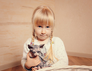 Cute little girl cuddling a small sphynx kitten