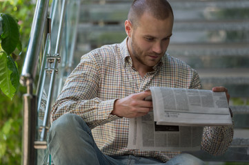 Man reading a newspaper and thinking