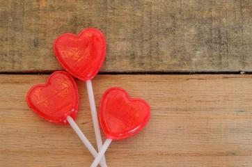 Red heart shaped lollipops on wooden pallet