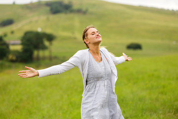 young woman with arms open on grassland