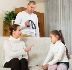 Parents scolding daughter at home
