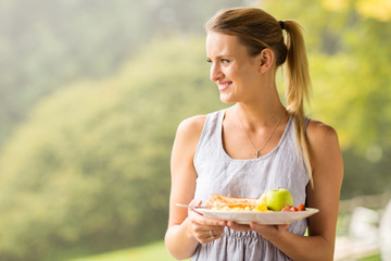 young woman holding plate of breakfast