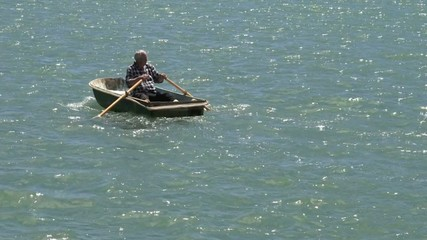 Slow motion of a man rowing a row boat at sea