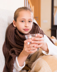 Girl in warm scarf drinking from glass