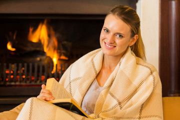 woman sitting near fireplace reading book