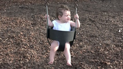 Slow motion of a baby girl on a swing at the playground