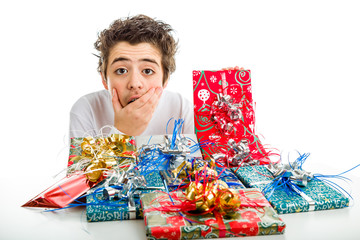 Amazed Boy holds his chin while receiving Christmas gifts