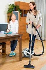 Girl helps mother to clean room