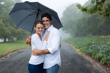young couple under an umbrella in the mist