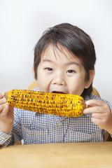 トウモロコシを食べる子供