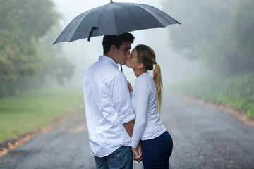 young couple in love under umbrella in the rain