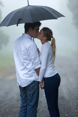 boyfriend and girlfriend kissing in the rain