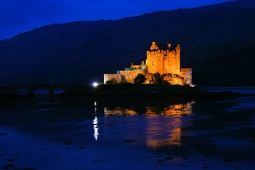 Eilean Donan Castle lit up at night in the highlands of Scotland