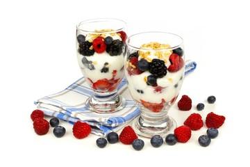 Healthy mixed berry, granola and yogurt parfaits on white