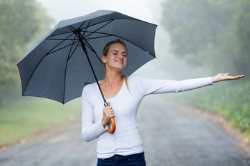 woman with umbrella enjoying the rain