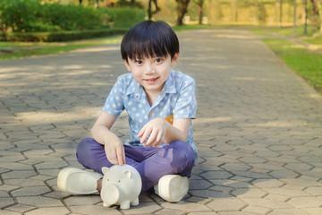 Little asian boy saving money in piggy bank on the road
