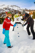 Winter fun, happy family playing with snowman