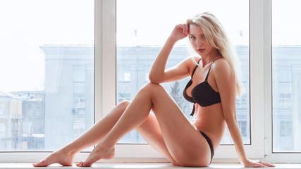 Young woman in underwear sitting on windowsill.