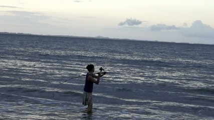 Slow motion of a young woman casting rod fishing at sunset