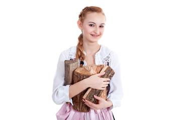 Junge Frau im Dirndl bringt Brennholz
