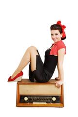 junge Frau sitzt auf altem Radio
