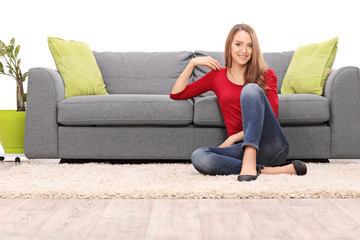 Beautiful woman sitting by a sofa on the floor