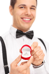 Close up on a young man holding an engagement ring