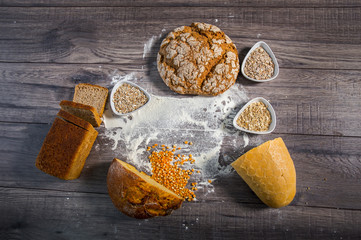 Group of different types of bread on old wooden table