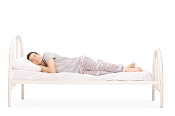 Happy young man sleeping in a bed