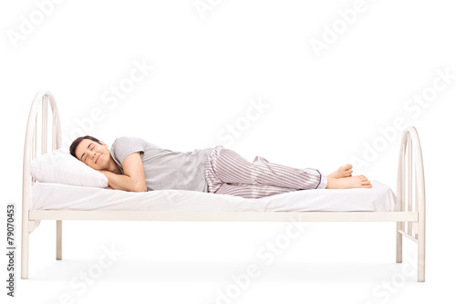 Happy young man sleeping in a bed - 79070453