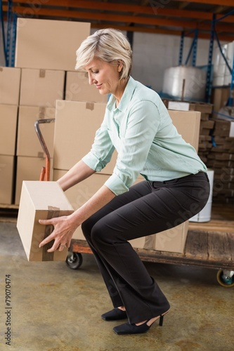 Warehouse manager picking up cardboard box - 79070474