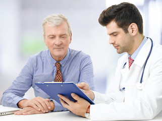 Portrait of young male doctor with elderly patient at hospital