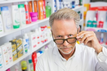 Serious pharmacist holding his glasses