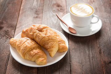 Fresh baked croissants and coffee on wood table