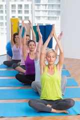 Women practicing yoga in fitness class