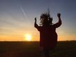 Frau hüpft Richtung Sonne