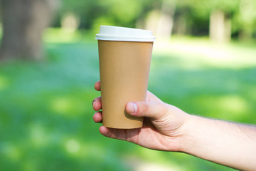 Disposable coffee cup on table on man's hand