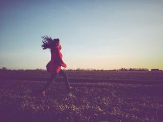 fröhliche Frau springt übers Feld