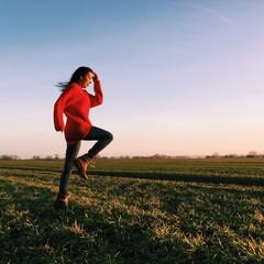 fröhliche Frau springt über eine Wiese