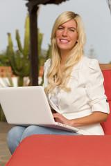 Junge hübsche Frau draussen am Laptop