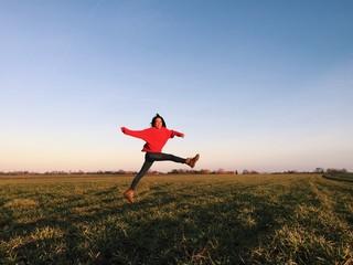 Frau springt über ein Feld